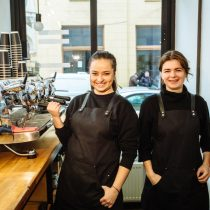 Two laughing real people female baristas in black uniform laughing, standing together in their workplace. Business partners stand behind the counter at coffee shop. Coworking concept